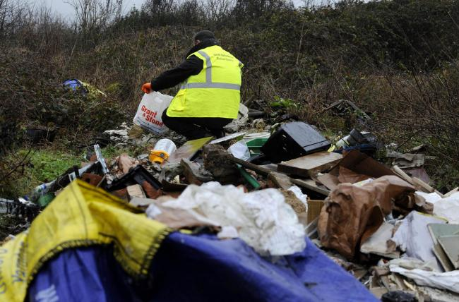 A council environmental health officer wades through a pile of rubbish near Headington (file image)
