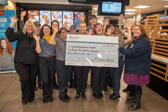 Staff with the cheque for Ronald McDonald House
