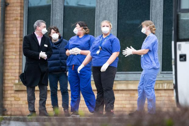 Herald Series: Members of staff wait as coaches carrying Coronavirus evacuees arrive at Kents Hill Park Training and Conference Centre, in Milton Keynes. Picture: Aaron Chown/PA
