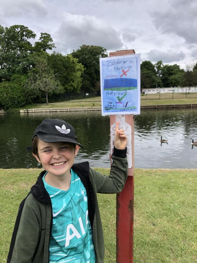 Harry Cousins, nine and his river poster on Abby Meadows.