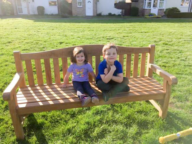 The Dominique Hill memorial bench on the green at Edington Place. Sat on it are Elodie and William Heley, children of Mrs Hill's friend Megan Heley. Picture: Megan Heley