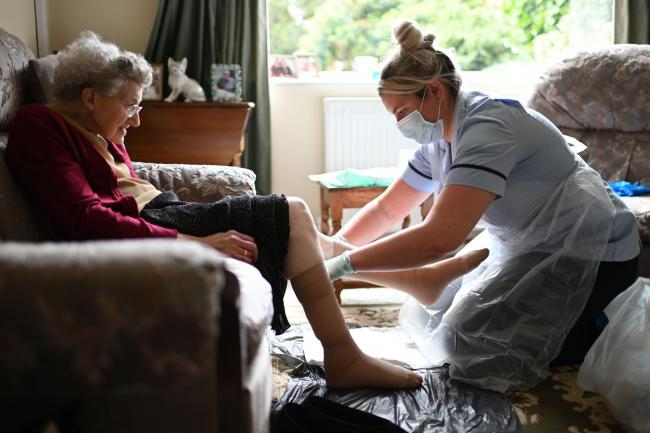 A nurse, wearing personal protective equipment (PPE), changing the dressings on the legs of an elderly woman during a home visit. Picture PA