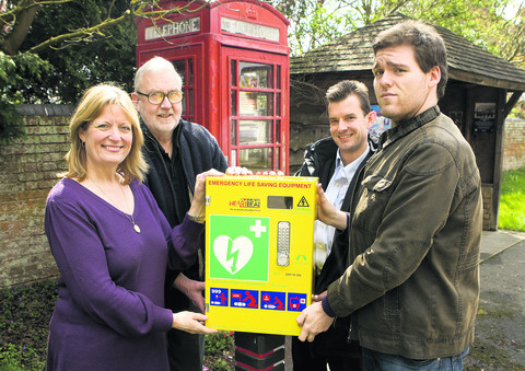 Beth Chesney-Evans and Crispin Evans, left, the parents of Guy, with his twin brother Charles, right, and Tom Bowtell of the parish council, with the defibrillator at the village phonebox