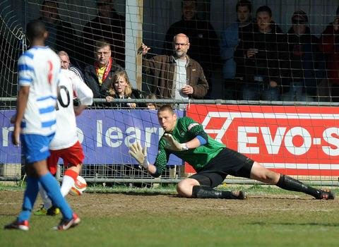 Oxford City keeper Jason Mooney dives to save a penalty against Brackley