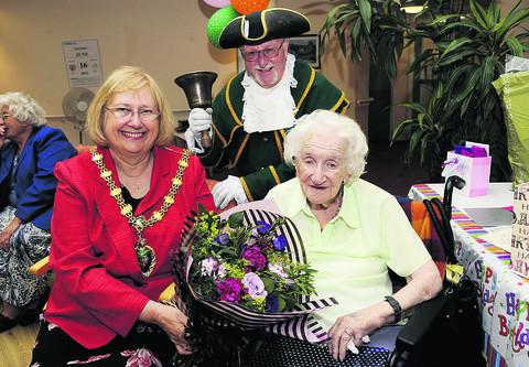 Doris Hyde receives flowers from the Mayor of Abingdon, Monica Lovatt, as town crier Peter Green looks on