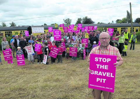 Herald Series: Mark Gray, front, and other campaigners beside the railway line