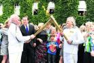 Cancer campaigner Clive Stone, left, transfers the flame to Roland Read, of Oxford