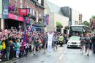 Raymond Blanc leaps with the flame on St Martin's Street, where crowds lined the pavements