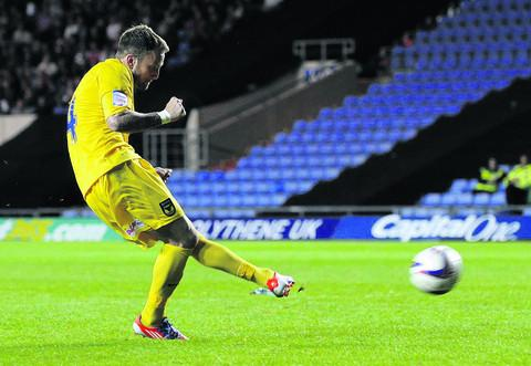 Sean Rigg tucks home his first-ever penalty during Oxford United's shoot-out on Tuesday night