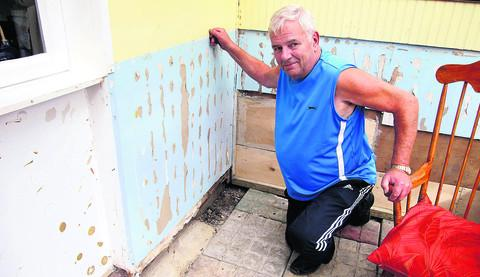 Roger Brazier shows some of the damage to the walls and floor of the conservatory in his house