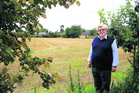 Brian Forster, chairman of Kingston Bagpuize Parish Council, and the land owned by St John's College on which developers want to build 63 homes. Picture: OX54106 Ric Mellis