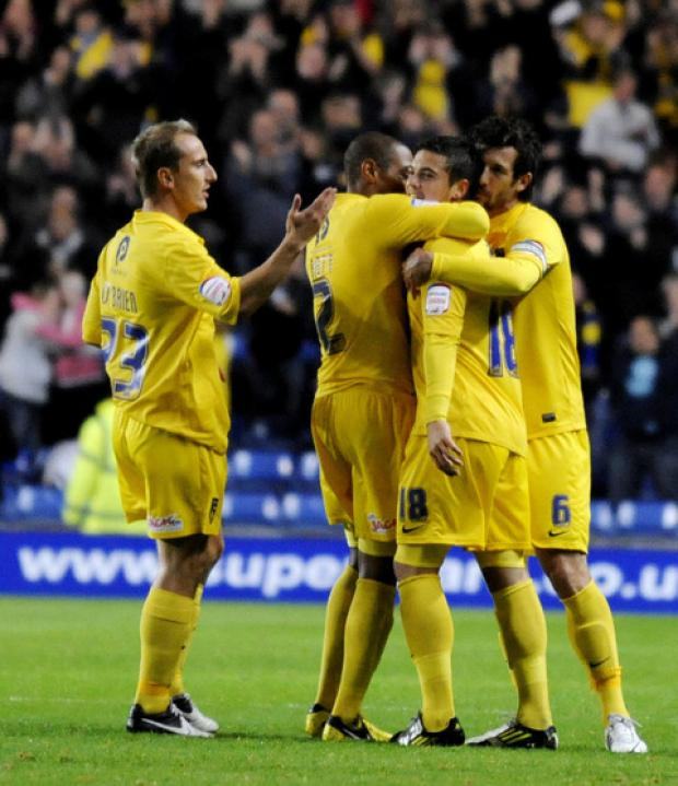 Jake Forster-Caskey (No 18) is mobbed by Luke O'Brien (left), Damian Batt and Jake Wright after his free-kick goal against AFC Wimbledon