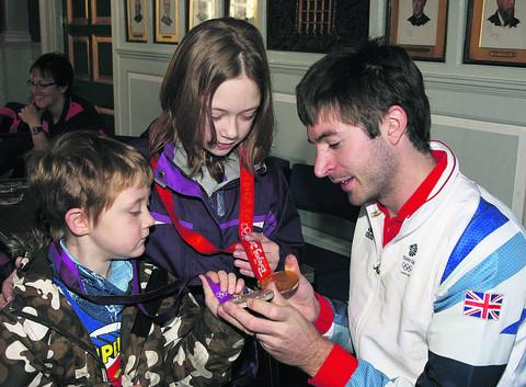 Zac Purchase shows his Olympic gold and silver medals to Elliot, five, and Bethany Price, 10. Picture: OX55253 Steve Wheeler
