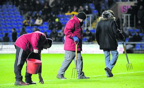 Groundsmen make running repairs at half time in a U's game