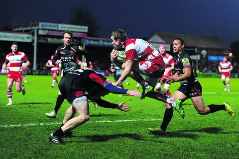 Gloucester's Steph Reynolds jumps a tackle from London Welsh's Jamie Stephenson