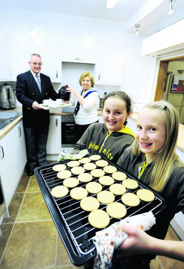 Herald Series: Ron Hill, committee chairman, and Norah Lunn, hall secretary, are ready for their tea and biscuits in the new kitchen as Yasmin Pearce, left, and Ellie Mitchell, of the 4th Grove Brownies, get ready to serve