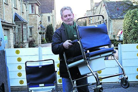 Herald Series: Philip Simms loads equipment from The Old Prebendal House care home in Shipton-under-Wychwood