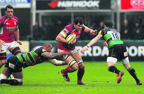 London Welsh's Ed Jackson sets off on a run as two Northampton men try to catch him