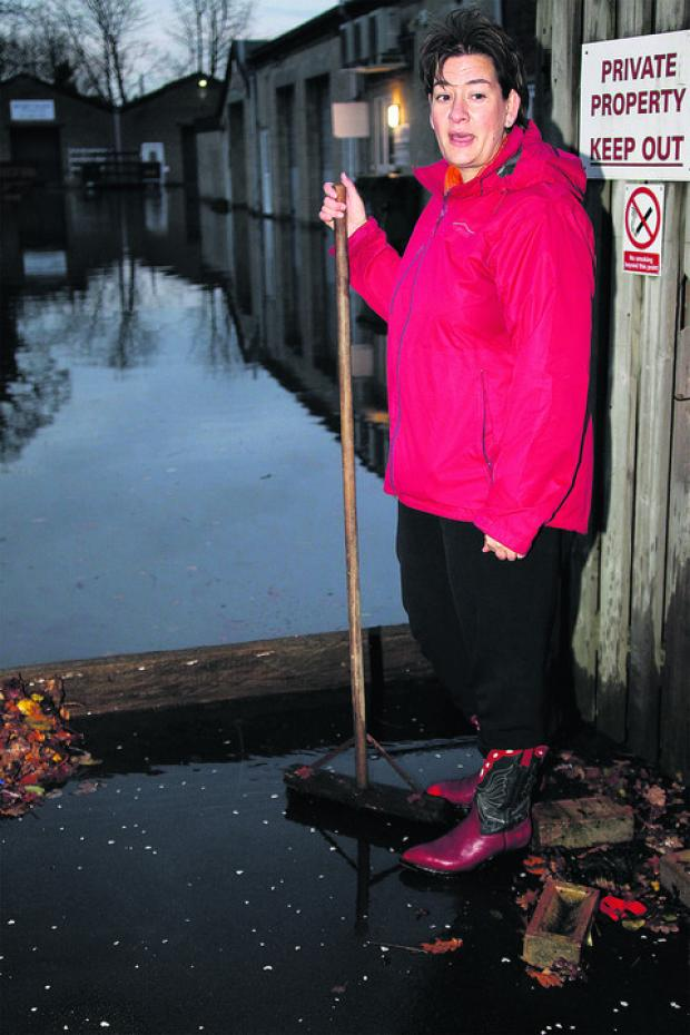 Bridge Street resident Lorraine Brodrick tries to keep on top of the rising water outside her home                      Picture: OX55873 Ric Mellis