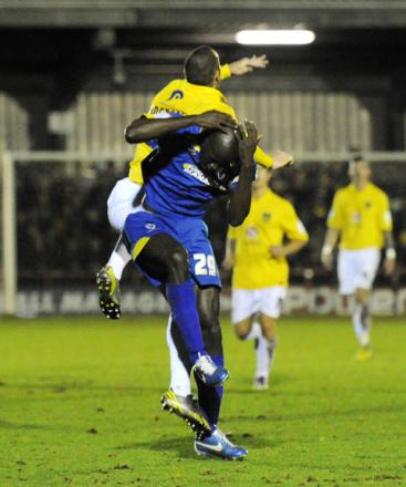 Wimbledon's Will Antwi takes avoiding action as he and James Constable go up for a high ball. The Oxford United strriker was sent off for dangerous use of the elbow, for which he will receive a four-match ban, if the club's appeal fails
