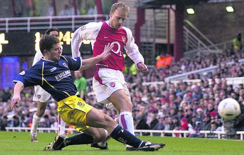 Scott McNiven tackles Dennis Bergkamp at Highbury in 2003, United's last third-round tie