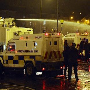 Herald Series: Police use water cannon in Belfast to disperse loyalists in the ongoing Union flag protests