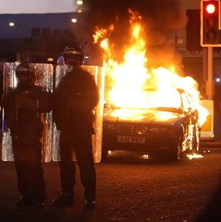 Herald Series: Riot police stand next to a burned out car after loyalist protesters attacked police lines in east Belfast