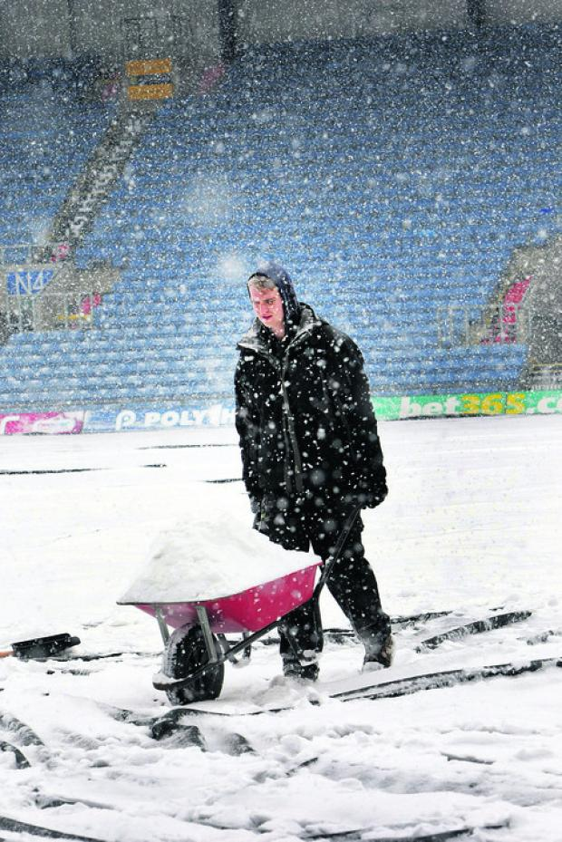 Groundsman Rory Moore tries to clear snow off the Kassam Stadium pitch yesterday