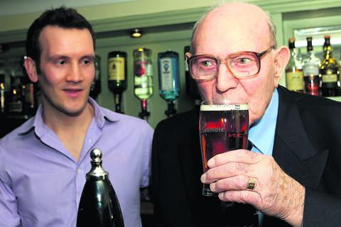 Stan Bradford takes his first sip of the beer named after him – Gunner's Gold – watched by Will Thompson, deputy manager of the Nag's Head in Abingdon. Picture: OX57311 Ric Mellis