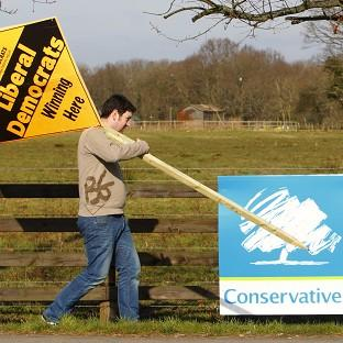 Herald Series: A Liberal Democrat supporter passes a Conservative banner as he prepares to erect a party advertisement in Eastleigh, Hampshire