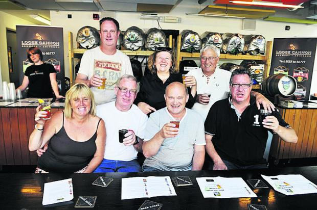 CHEERS: Front from left, Debbie Scott, Mick Rayner, Nigel Foster, Gary Vass and, back from left, Paul Rowley, Jayne Matthews, David Matthews, Didcot Beer Festival at the Cornerstone Arts Centre Picture: OX60935 Mark Hemsworth