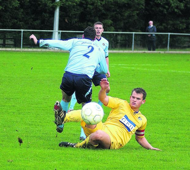 Abingdon United's Shawn Foster slides to clear the ball during their 4-0 defeat by Ardley United on Saturda