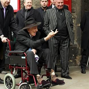 Herald Series: Ronnie Biggs gestures to the waiting press at the funeral of Bruce Reynolds, the mastermind behind the Great Train Robbery of 1963, at St Bartholomew The Great church in Smithfield, London.