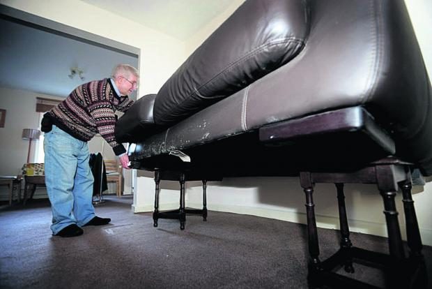 Herald Series: Andrew Ivett checks his sofa placed on tables as flood waters rise around his home in Earl Street