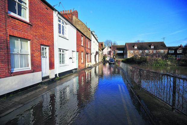 Herald Series: UNDER WATER: Thames Street, Abingdon, flooded after heavy rainfall and the scene at St Helen's Mill Bridge, below