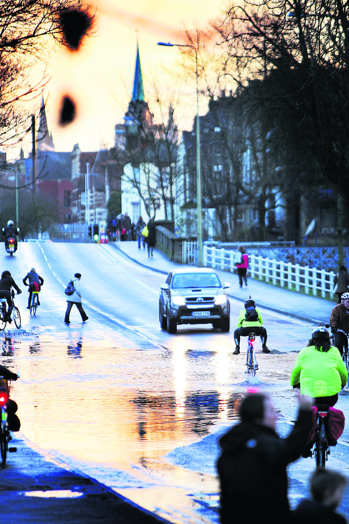 One of the few cars to brave Botley Road waits as a cyclist goes through the floods, legs held up to avoid a soaking