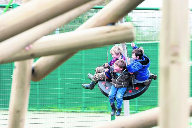 Herald Series: Boys enjoy a ride on a new swing