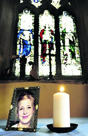 A candle burns next to a portrait of Jayden Parkinson at Didcot's All Saints Church
