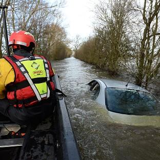 Herald Series: Members of the Avon and Somerset Police Underwater Search Unit inspect a submerged car near Muchelney in Somerset