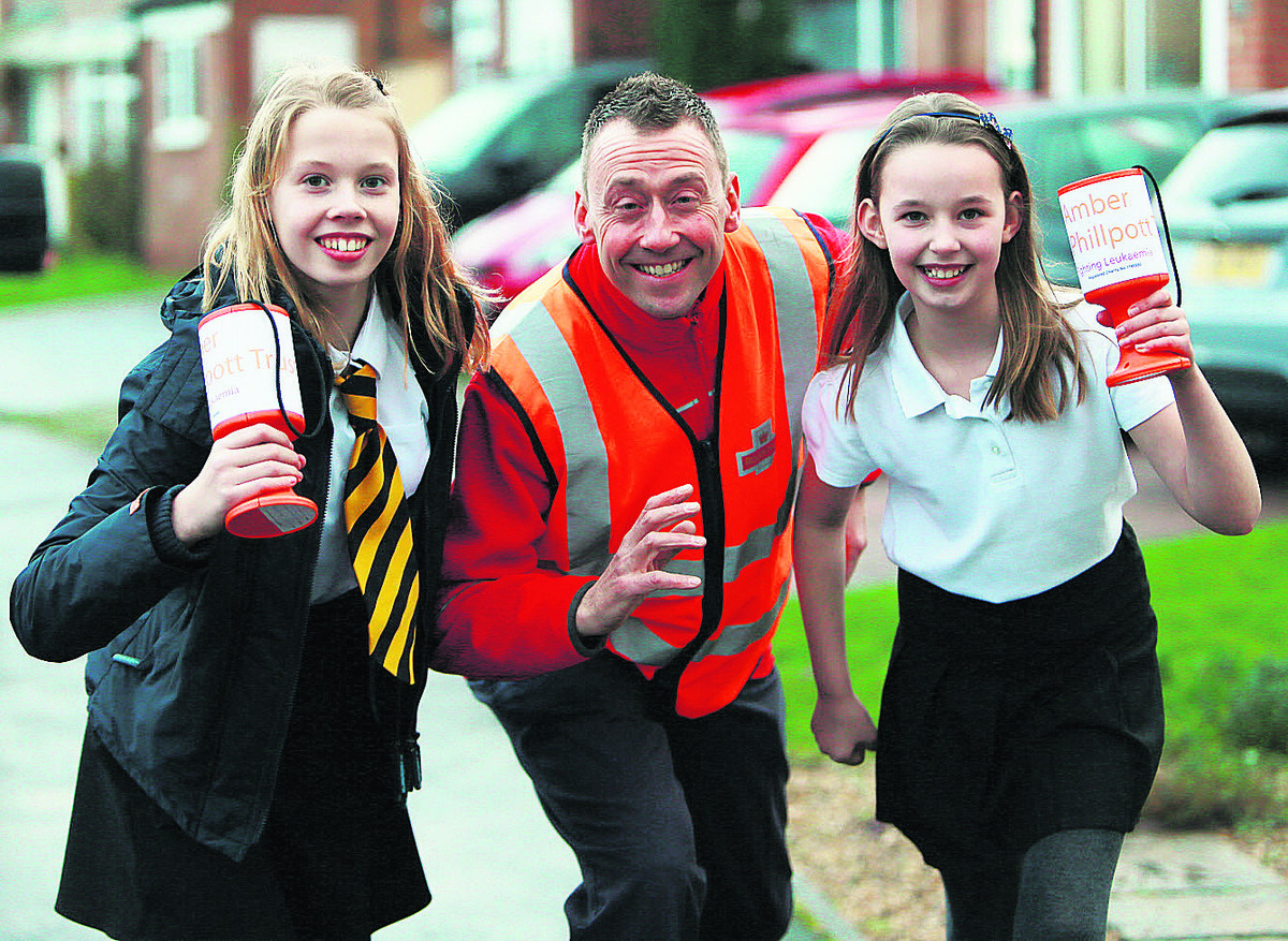Postman Justin Lovstrom with Freya, 12, left, and Phoebe, nine. Picture: OX64892 Damian Halliwell