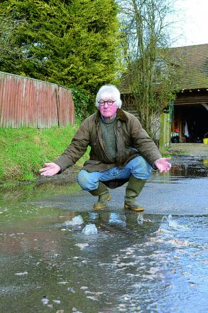 Frank Dumbleton shows sewage coming out of a manhole cover in The Lane, Chilton