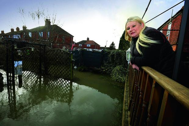 Herald Series: Jayne Madden surveys her flooded garden in Weirs Lane, off Abingdon Road, Oxford.