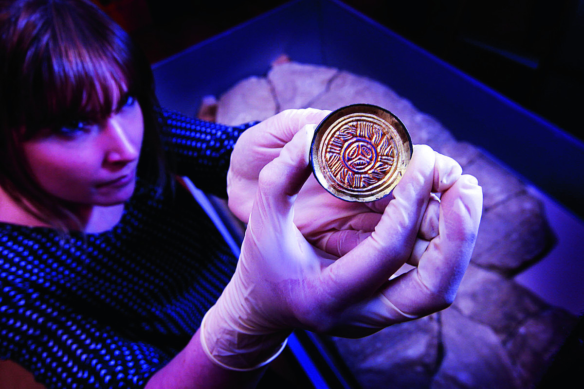 Project Officer Anna Griffiths with one of a pair of Ango-Saxon saucer brooches from 500-600 AD found at Watchfield. Picture: OX65095 Ed Nix