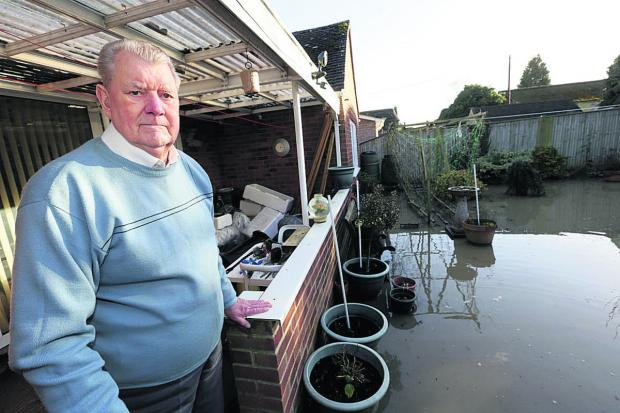Percy Buckingham surveys flooding outside his home. Picture: Damian Halliwell