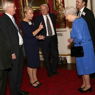 Queen Elizabeth II (right) meeting Dame Helen Mirren, as Sir David Attenborough (third left) looks on, during a Reception for the Dramatic Arts, at Buckingham Palace, London.