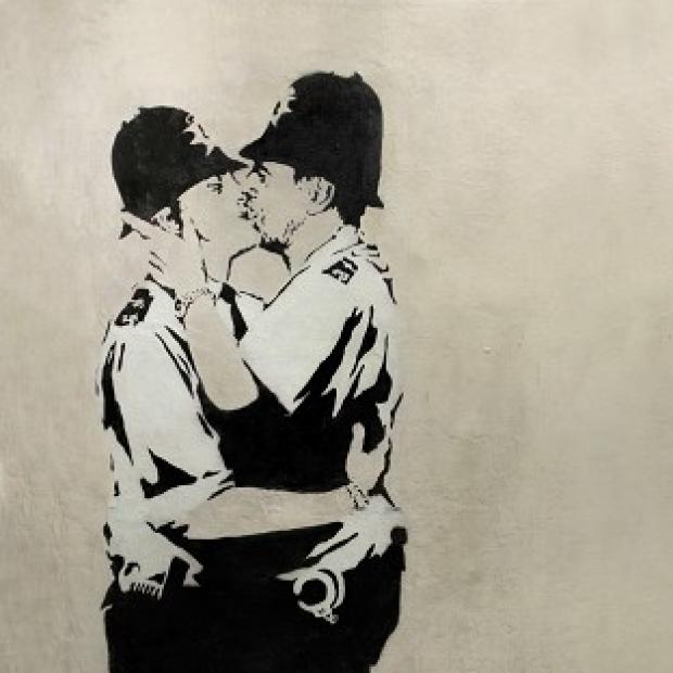 "Herald Series: ""Kissing Coppers,"" a black-and-white stencil of two uniformed policeman in a passionate clinch by Banksy."