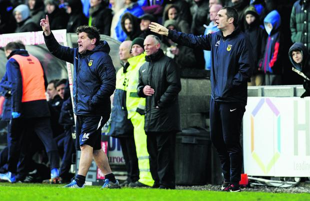 Oxford United's caretaker manager, Mickey Lewis (left), and first-team coach Andy Melville on the touchline urging their side to make the most of their remainin