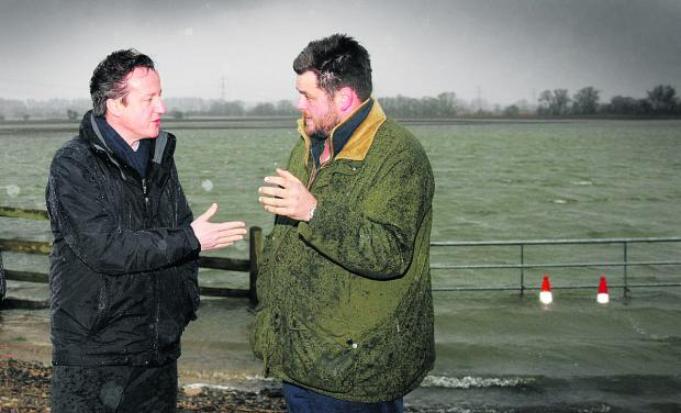 David Cameron visits farmer Tim Hook and his flooded fields last month. Picture: Damian Halliwell