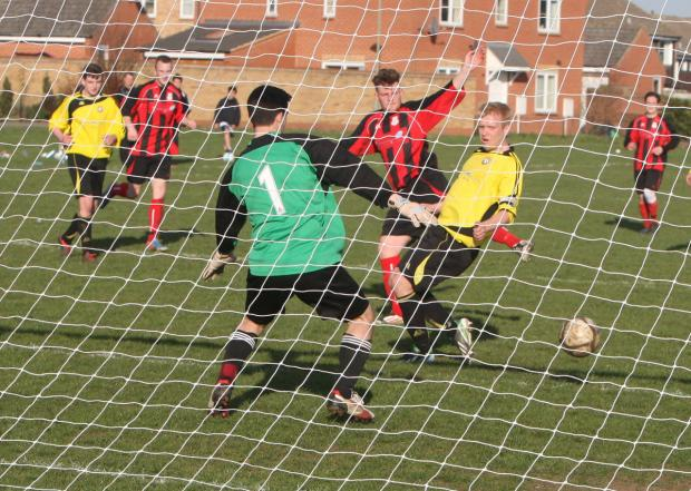 Berinsfield's Danny Brind (red) slots the ball past Long Wittenham goalkeeper Andy Griffiths