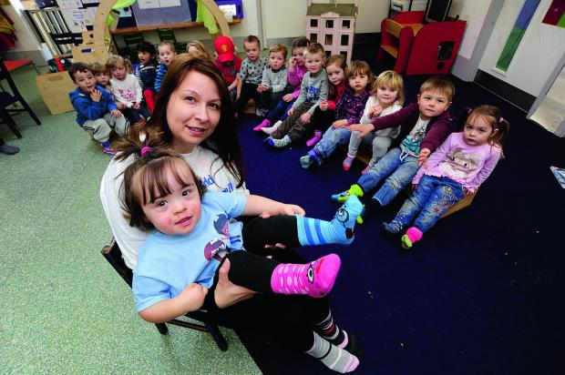 Herald Series: World Down's Syndrome Day is marked at Berinsfield Pre-School with all the children wearing odd socks. Front, Jo Crawford with her daughter Evie-Mae, two, wearing her odd socks, with her friends offering their efforts